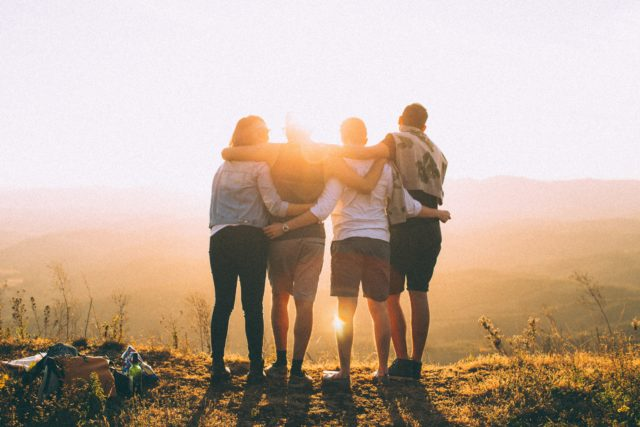 Ungdomar som håller om varandra i motljus