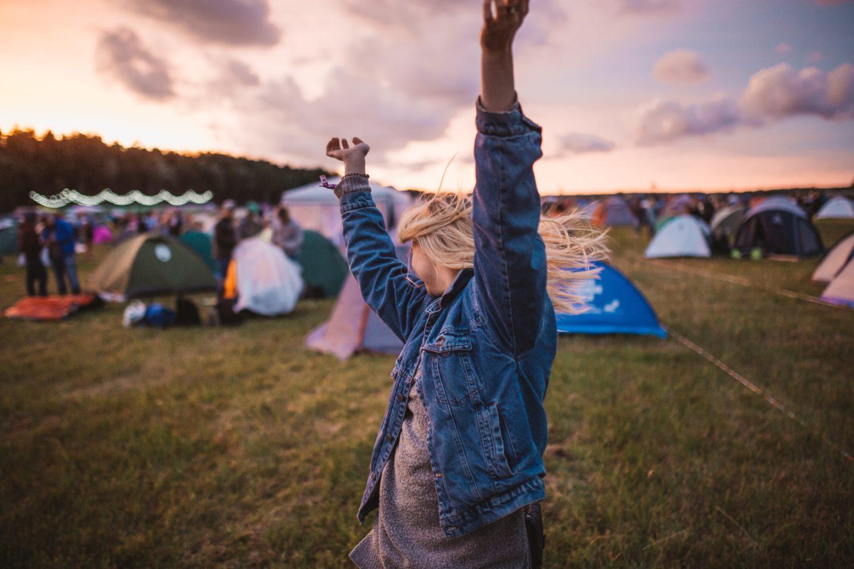 Scout som dansar med tält i bakgrunden